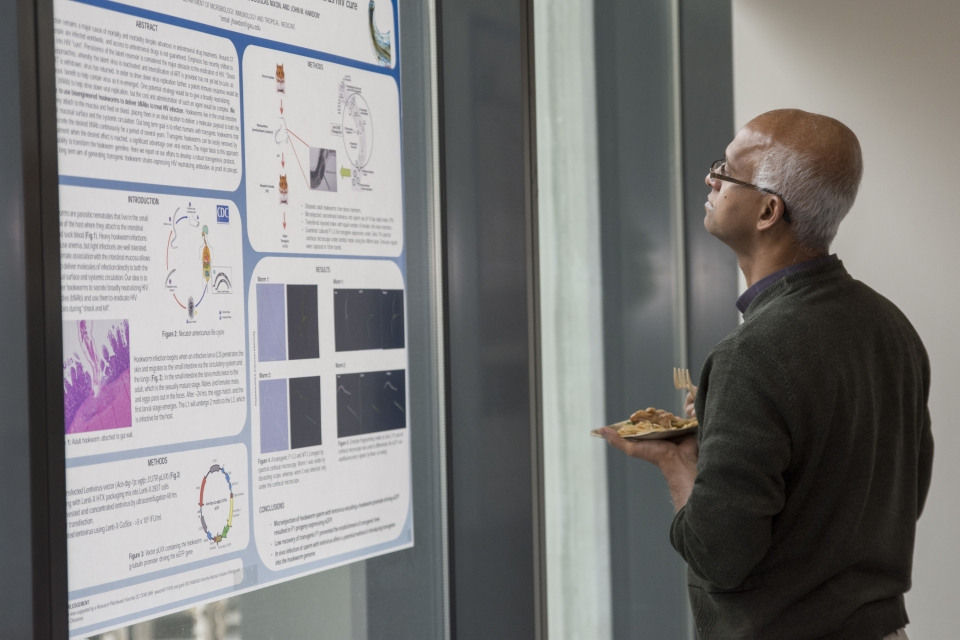 The guest observes a poster session and takes notes